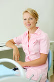 Young dentist sits at table and smiles Royalty Free Stock Photo