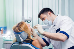 Young dentist working with the female patient in a modern hospital. royalty free stock images