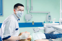 Young dentist working with the female patient in a modern hospital. royalty free stock photo