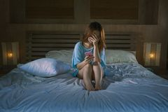 Young depressed Asian Korean girl using mobile phone crying on bed at night feeling sad and depressed victim of cyber bullying or. Broken heart suffering royalty free stock images
