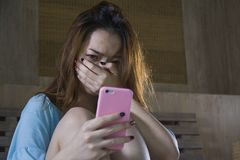 Young depressed Asian Korean girl using mobile phone crying on bed at night feeling sad and depressed victim of cyber bullying or. Broken heart suffering royalty free stock image