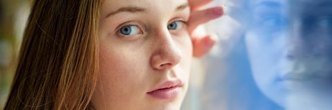 Young depressed lonely female college student standing by a window at her school, looking at the camera. Education, Bullying. royalty free stock photo