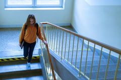 Young depressed lonely female college student walking down the stairs at her school, looking down. Education, Bullying, Depression concept Stock Photography