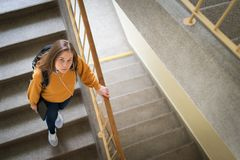 Young depressed lonely female college student walking down the stairs at her school, looking up at the camera. Education, Bullying, Depression concept Stock Images