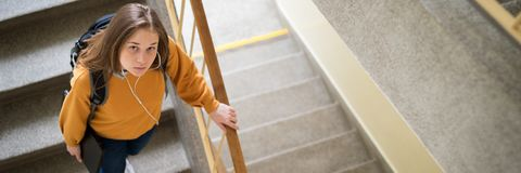 Young depressed lonely female college student walking down the stairs at her school, looking up at the camera. Education concept. stock photos