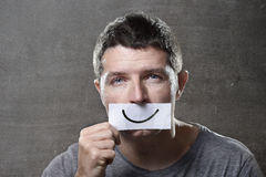 Young depressed man lost in sadness and sorrow holding paper with smiley on his mouth in depression concept. Young depressed man lost in sadness and sorrow Royalty Free Stock Images