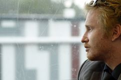 Young depressed man reflecting on life journey soul searching. A lonely young man sits alone on a bus staring out the window unaware of the image being taken stock images