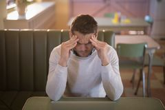 Depressed man sitting in restaurant. Young depressed man sitting in restaurant Royalty Free Stock Photo