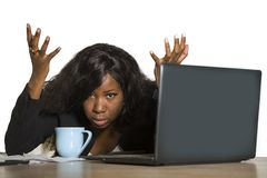 Young depressed and overwhelmed black African American business woman working frustrated at office computer desk feeling upset and royalty free stock photography