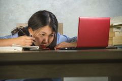 Young depressed and stressed Asian Chinese student girl working with laptop and book pile overwhelmed and frustrated preparing exa royalty free stock images