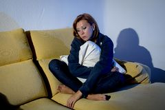 Young depressed woman on couch with pillow cushion crying alone in stress Royalty Free Stock Photos