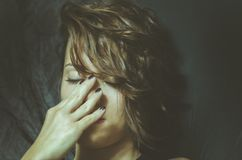 Young depressed woman feeling miserable and lonely cover her face with her hands in the dark room of her home. Stock Image