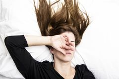 Young depressed woman is lying in her bed, covering her face with her hands. Royalty Free Stock Photography