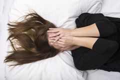 Young depressed woman is lying in her bed, covering her face with her hands. Sorrow concept Royalty Free Stock Images
