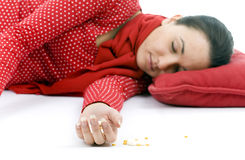 Young depressive woman lying on red pillow Royalty Free Stock Images