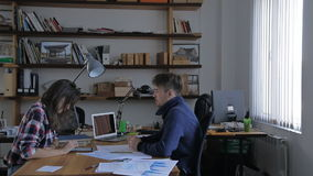 Young design Attractive team working at desk. Modern team of two partners sitting at a wooden table and exchange ideas, views, lots of talk, make notes in a stock video footage