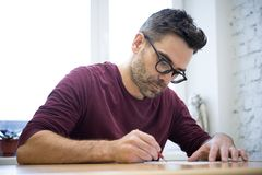 Young Designer Drawing the Sketch Using Pencil on the Wooden Table in Bright Studio Royalty Free Stock Photos