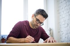 Young Designer Drawing the Sketch Using Pencil on the Wooden Table in Bright Studio Stock Photos