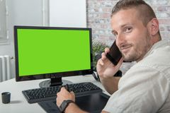 Young designer man uses a graphic tablet and phone, green screen. A young designer man uses a graphic tablet and phone, green screen royalty free stock photography