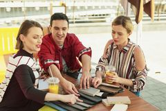 Young designer meeting with clients at cozy cafe. Cozy cafe. Young designer meeting with clients at cozy cafe that showing several colors of textile for curtains stock image