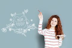 Young designer smiling while drawing a lovely owl. Lovely detail. Beautiful talented creative designer smiling and carefully holding a brush while painting a royalty free stock photo