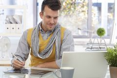 Young designer using drawing pad smiling Royalty Free Stock Image