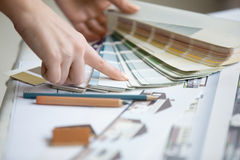 Young designer working with color palette. Creative people workplace. Close-up view of hands of young designer woman working with color palette at office desk royalty free stock image