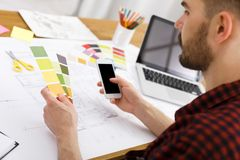 Young designer working with color palette office. Young designer in casual working with color palette and smartphone in modern workplace interior, copy space royalty free stock photos