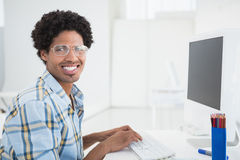 Young designer working at his desk smiling at camera Stock Image
