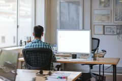 Young designer working late at his desk in an office Royalty Free Stock Photo