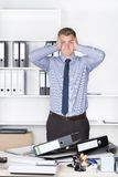 Young despaired man is standing in front of many files Stock Image