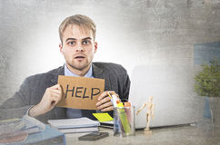 Young desperate businessman holding help sign looking worried suffering work stress at computer desk Royalty Free Stock Photography