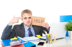 Young desperate businessman holding help sign looking worried suffering work stress at computer desk. Young desperate businessman holding help sign looking Royalty Free Stock Image