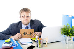 Young desperate businessman holding help sign looking worried suffering work stress at computer desk. Young desperate businessman holding help sign looking Royalty Free Stock Images