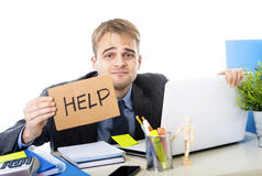 Young desperate businessman holding help sign looking worried suffering work stress at computer desk. Young desperate businessman holding help sign looking Stock Image