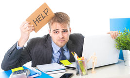 Young desperate businessman holding help sign looking worried suffering work stress at computer desk Stock Images