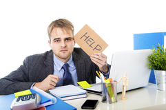 Young desperate businessman holding help sign looking worried suffering work stress at computer desk. Young desperate businessman holding help sign looking Stock Photo