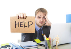 Young desperate businessman holding help sign looking worried suffering work stress at computer desk. Young desperate businessman holding help sign looking Stock Photography