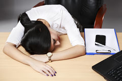 young desperate businesswoman sleeping on desk in office Stock Photography