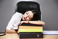 Young desperate businesswoman sleeping on desk in office Royalty Free Stock Image