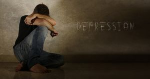 Young desperate and depressed man crying alone with the word depression written on the wall stock photography
