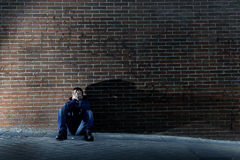 Young desperate man who lost job lost in depression sitting on ground street corner Royalty Free Stock Photography