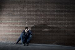 Young desperate man who lost job lost in depression sitting on ground street corner Stock Images