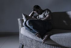 Young desperate sad and frustrated man grieving at home sofa couch suffering depression problem and anxiety crisis crying helpless. In pain feeling sick and stock photography