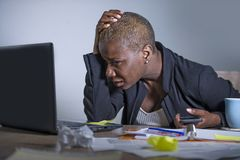 Young desperate and stressed african american business woman working at laptop computer desk at office suffering stress feeling sa stock photography