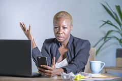 Young desperate and stressed african american business woman working at laptop computer desk at office suffering stress problem us. Ing mobile phone overwhelmed stock photo