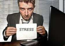 Young desperate and stressed business man working overwhelmed at office computer desk feeling helpless and overworked holding royalty free stock images