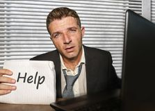Young desperate and stressed business man working overwhelmed at office computer desk feeling helpless and overworked holding. Notepad asking for help in royalty free stock image