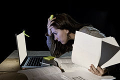 Young desperate university student girl in stress for exam studying with books and computer laptop late at night Royalty Free Stock Images
