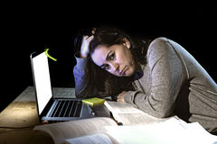 Young desperate university student girl in stress for exam studying with books and computer laptop late at night Royalty Free Stock Photography